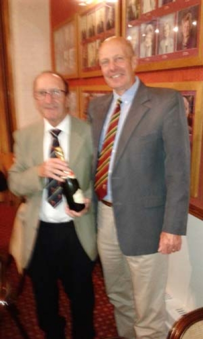 Rolls Seniors Captain presenting Emlyn with a bottle of Champagne.